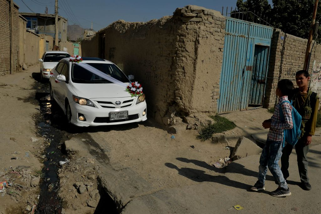 Boys look at a car decorated with flowers parked along a house for a wedding ceremony in Kabul on September 27, 2021. (Photo by Hoshang Hashimi / AFP) (Photo by HOSHANG HASHIMI/AFP via Getty Images)