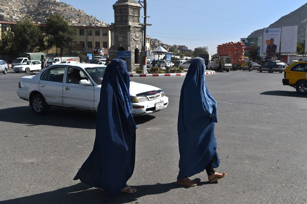 Women wearing a burqa walk near the site where a grenade was thrown at a Taliban vehicle at the Deh Mazang Circle in Kabul on October 20, 2021. (Photo by WAKIL KOHSAR / AFP) (Photo by WAKIL KOHSAR/AFP via Getty Images)